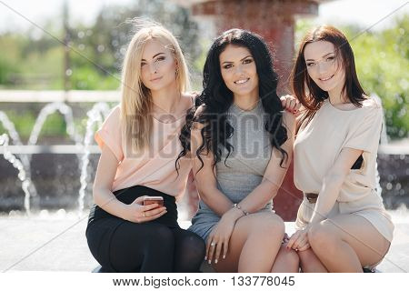 Funny girlfriend,three cute girls, brunette,blonde and girl with black long curly hair,nice smile,light makeup,wear jewelry,posing,sitting together outdoors in the Park near the fountain in summer Sunny day