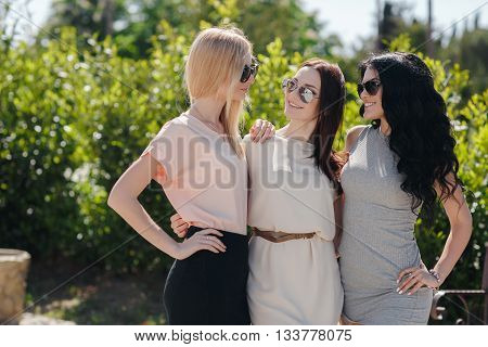 Funny girlfriend,three cute girls, brunette,blonde and girl with black long curly hair,nice smile,light makeup,wear jewelry and sun glasses,posing,standing together outdoors in the Park on a background of green plants in the summer