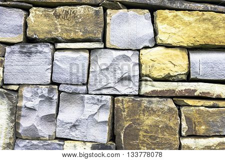 Textured limestone stone wall  with grey and yellow stones