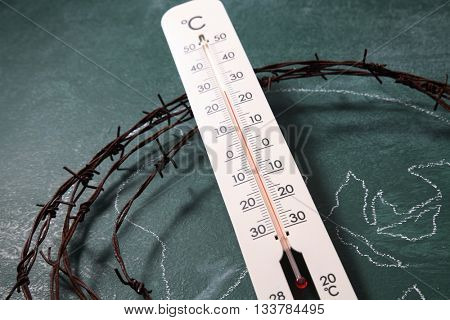 drawing world map  and thermometer surrounding by the barbwire - global warming concept