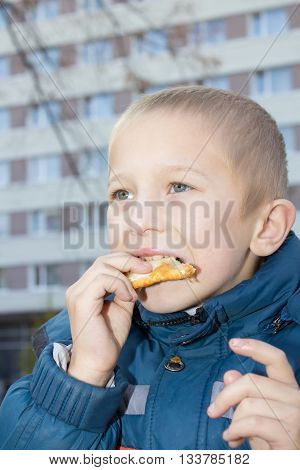 delicious pasties with meat eating boy in city street