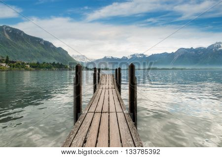 Switzerland landscape - Wooden pier in lake at Switzerland. Beautiful lake in Switzerland.