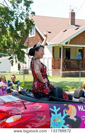 WEST ST. PAUL, MINNESOTA - MAY 21, 2016: Princess of South Wind for St. Paul Winter Carnival Peggy Ly waves to crowd at annual Grande Parade in West St. Paul on May 21.