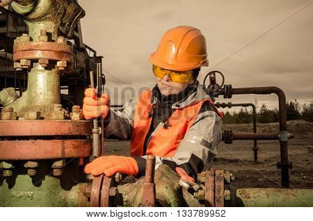 Woman engineer in the oil field repairing wellhead with the wrench wearing orange helmet and work clothes. Oil and gas concept. Toned.