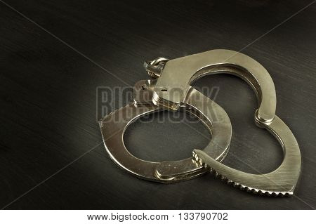 Metal police handcuffs on a dark wooden board. Silver handcuffs. Security concept on wooden background. Closed handcuffs. Equipment police officer. Crime and Punishment. poster