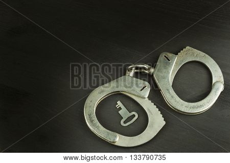 Metal police handcuffs on a dark wooden board. Silver handcuffs. Security concept on wooden background. Closed handcuffs. Equipment police officer. Crime and Punishment.