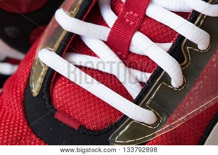 Youth red sneaker with white untied the laces close-up