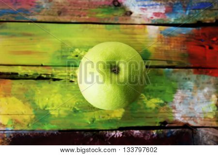 Photo of green apple on yellow wooden background