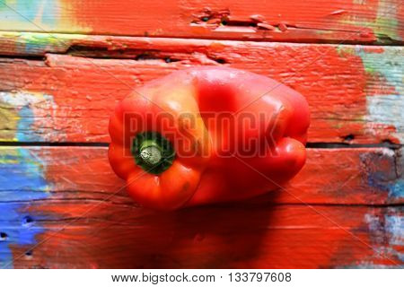 Photo of red pepper on red wooden background
