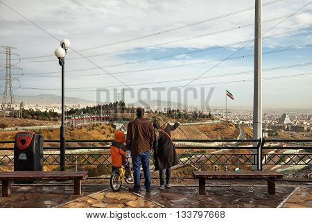 TEHRAN IRAN - FEBRUARY 11 2015: Iranian family with their son staring at skyline of Tehran from a high ground Park. Tehran is capital of Iran and its most populated city.