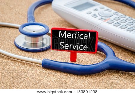Phone and stethoscope on the table with Medical service words on the board. Medical concept.