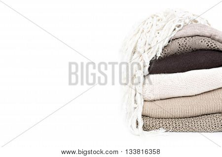 stack of brown woolen knitted sweaters isolated on white background copy space