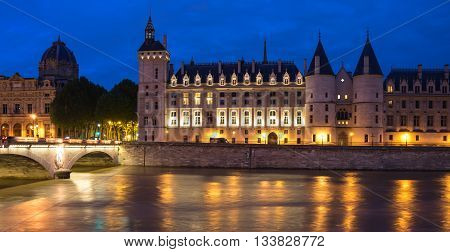 Night view of La Conciergerie (old medieval jailhouse) and the Seine river Paris France