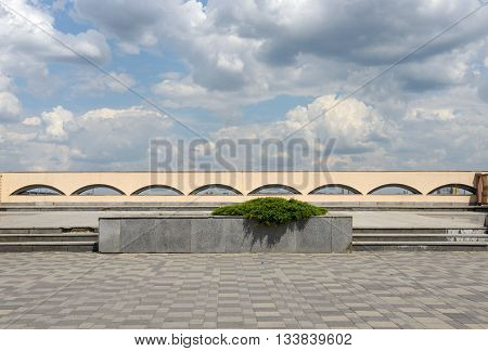 Scenic cloudscape above pavement and parapet of Dnieper River embankment in sunlight in Dnepropetrovsk Ukraine.