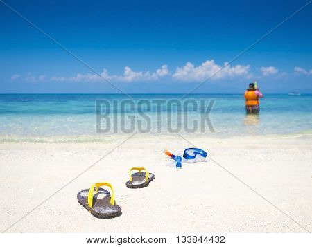 flip flop and dive equipment on white sand beach in the sea shore