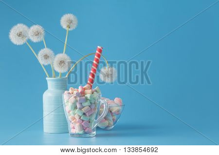 Sweet candies on blue color table with dandelions
