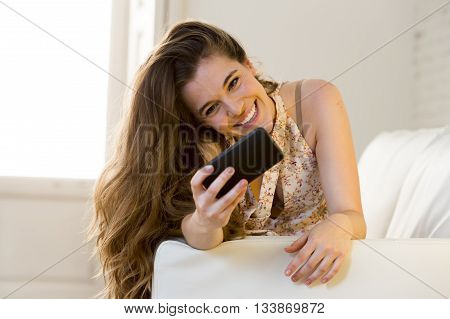 young beautiful girl lying at home sofa couch relaxed holding mobile phone using internet at apartment living room smiling happy and laughing while reading or watching something funny
