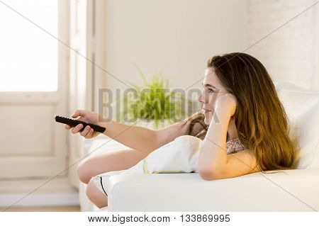 young beautiful woman lying at her apartment living room on sofa couch holding remote control watching television happy and relaxed in girl enjoying TV concept