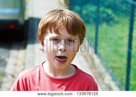 cute young boy in red shirt shows his tongue