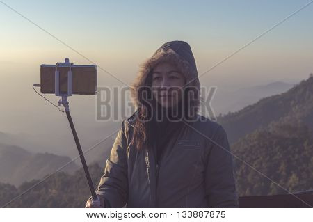 Women selfie with mobile smart phone with a background mountain in the morning before sunrise.