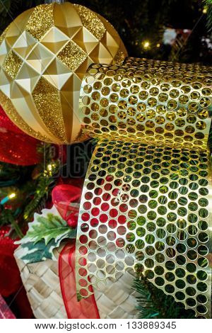 Christmas metallic perforated ribbon as decorative ornament, in among other festive items. Perforation is round in shape. Tungsten lighting gives the image a warm feel.