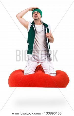 Surprised man dressed like a gnome sitting on red bag with gifts. Isolated over white background in full length.