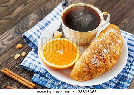 Continental breakfast - cup of hot coffee croissant and orange. Tasty food on plaid blue napkin rustic wooden background.