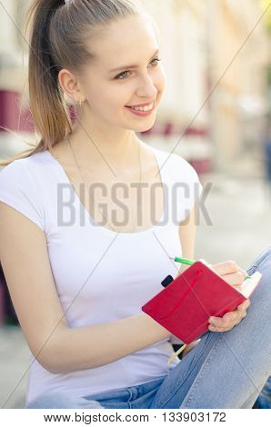 Attractive Young Woman Writting In Notebook In The City