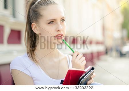 Attractive Young Woman Thinking Writting In Notebook