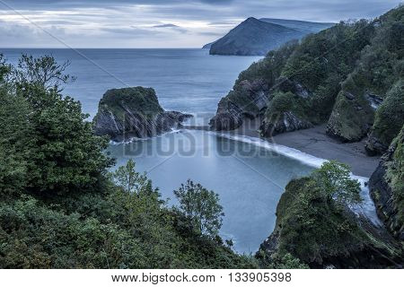 Beautiful Dramatic Sunrise Landsape Image Of Small Secluded Cove At Combe Martin Bay