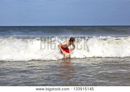 Young Boy Is Body Surfing In The Waves