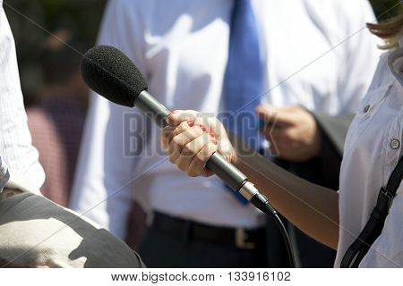 Reportert holding a microphone conducting an TV or radio interview