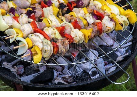 fresh shashlik skewers with onions peppers and meat above the charcoal embers on a small barbecue grill selected focus and very narrow depth of field