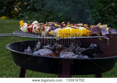 small old barbecue grill with glowing charcoal and shashlik skewes in the garden selected focus and narrow depth of field