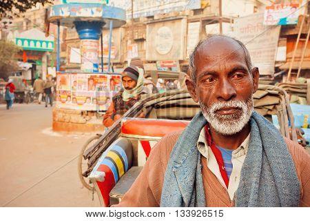 VARANASI, INDIA - JAN 1, 2016: Senior man with white beard standing on the busy street of Varanasi indian city on January 1, 2016. Varanasi urban agglomeration had a population of 1435113