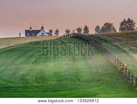 Whisps of Fog in Horse Country with barn on hill