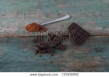 Dark chocolate and a spoon with cocoa on an old vintage table stock photo