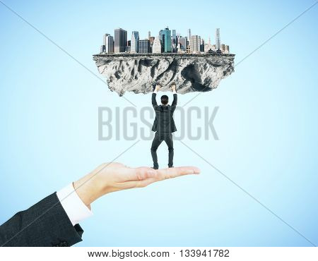 Businessman miniature standing on hand and upholding abstract city on blue background