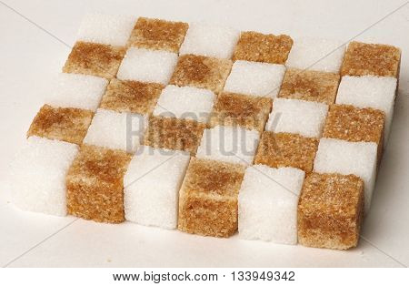 Cubes of sugar cane brown and white folded into a checkerboard pattern concept isolated