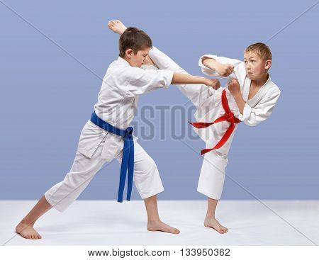 On a gray background athletes are training blows karate