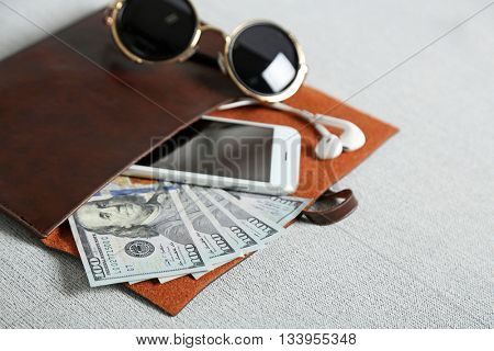 Leather purse with mobile phone, glasses and dollar banknotes on grey cloth background
