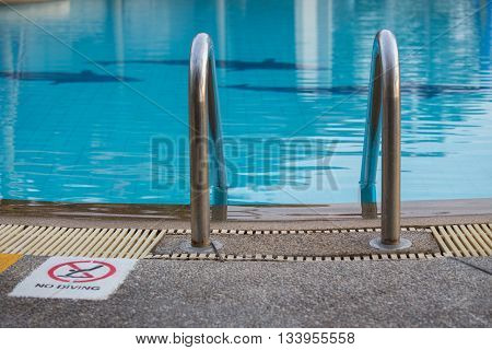 swimming pool with lader and warning sign