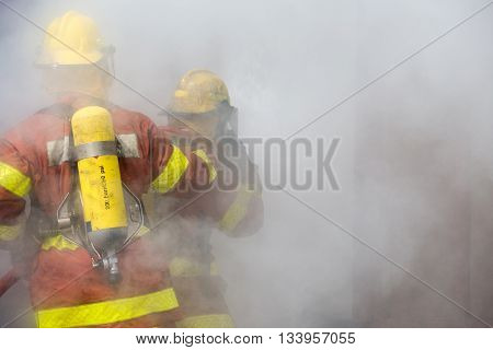 2 firemen in operation surround with smoke