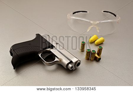 small gas pistol and cartridges on a gray background