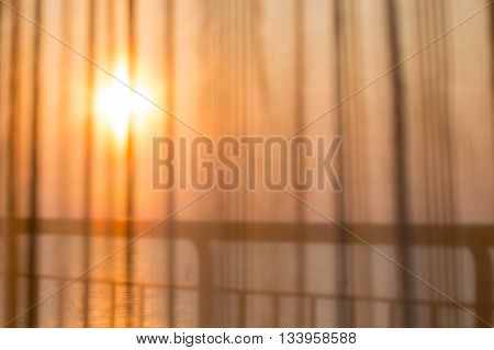 blurred of room curtain see through the sea background in sunrise on vacation