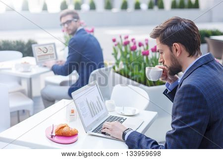 Handsome young businessman is drinking coffee in cafe. He is sitting at table and using a laptop with concentration. Man in suit in looking at him with curiosity on background