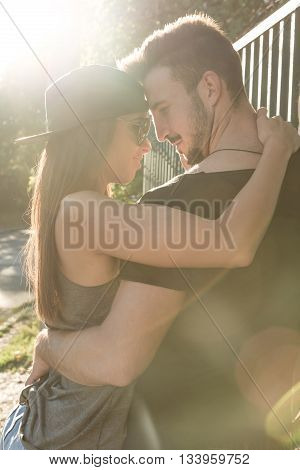 A young HipHop styled couple hugging next to a fence during sunset in a urban environment.