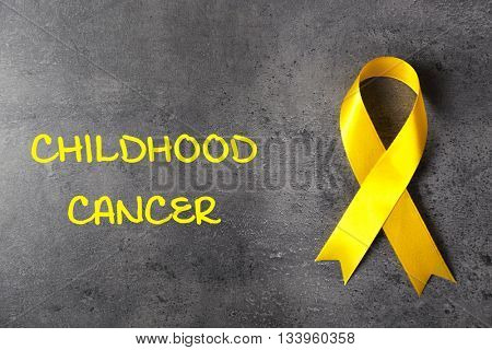 Yellow ribbon and text Childhood Cancer on grey textured background