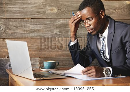 Worried African Businessman In Official Suit Checking Information In Laptop And Papers In Cosy Caf&#