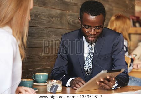 Team Work: Two Business People In Formal Wear Sitting Together At The Table And Discussing Something
